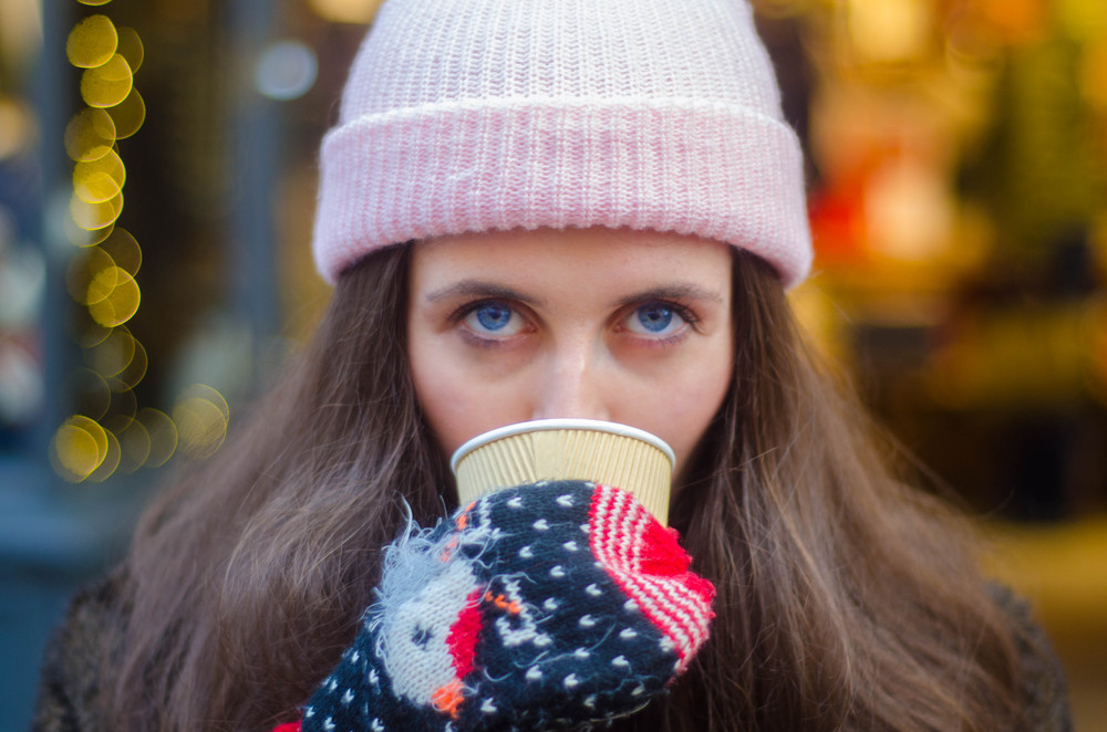 A lady drinks a cup of coffee